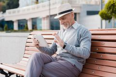 A pensioner sits on a bench in a beautiful square. He has a gray tablet in hands. He communicates by video with someone Stock Image
