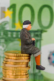 Pensioner sitting on cash pile Royalty Free Stock Photography