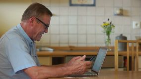 The pensioner is sitting in the kitchen and browsing his accounts using an internet and a laptop. Next to the table are. Bank cards, in the man`s hand holds a stock footage