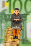 Pensioner sitting on pile of money Royalty Free Stock Image