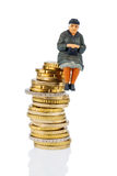Pensioner sitting on a pile of money Stock Photography