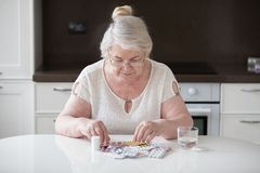The pensioner is sitting at the table and looking at his medication. stock image