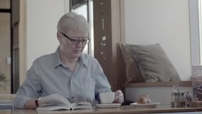 A pensioner spending time in cafes, reading an interesting book stock footage