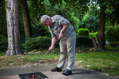 Pensioner starts to shot a minigolf ball at the court Royalty Free Stock Image