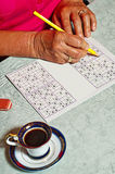 Pensioner with sudoku Stock Photography