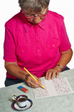 Pensioner with sudoku Stock Image