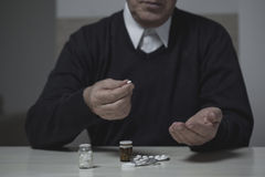 Pensioner taking pills Royalty Free Stock Images