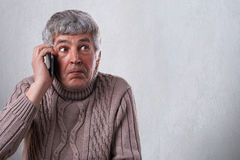A pensioner talking over smartphone being astonished to receive call. A surprised expression of mature man in sweater isolated ove. R white background holding Stock Images