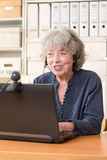 Pensioner telephoning via skype. Pensioner telephoning with her family via skype, copy space Stock Image