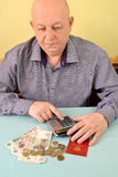 The pensioner thoughtfully counts money on the calculator.  Stock Photography