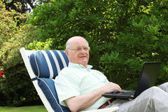 Pensioner using laptop in garden. Low angle view of a senior pensioner reclining on a comfortable lounger using a laptop in his lush leafy garden stock photography