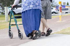 Pensioner with walking aid II. A disabled old woman is strolling along a footpath with a walking aid with her partner at her side Stock Images