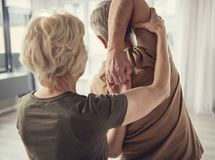 Pensioner woman helping to perform physical exercise. Oldish men standing with hands hooked behind his back. Mature lady assisting him Royalty Free Stock Image