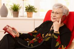 Pensioner woman using landline phone. Sitting in armchair in living room Royalty Free Stock Images