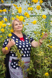 Pensioner woman in yellow flowers Stock Photo