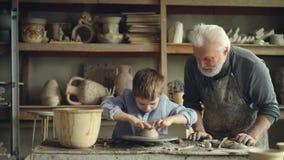 Pensionerad farfar som ger grunderna av krukmakeri till hans gulliga lilla sonson, medan arbeta tillsammans i slags tvåsittssoffa stock video