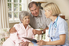 Pensionerad hög kvinna som har den vård- kontrollen med sjuksköterskan At Home royaltyfri bild