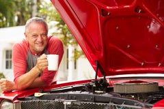 Pensionerad hög man som arbetar på den återställda klassiska bilen Arkivfoton