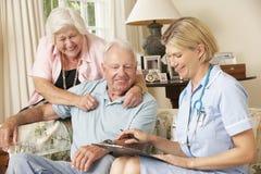 Pensionerad hög man som har den vård- kontrollen med sjuksköterskan At Home arkivfoto