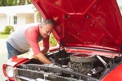 Pensionerad hög man som arbetar på den återställda klassiska bilen Royaltyfria Bilder
