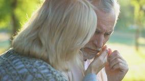 Pensionerad kvinna som dåligt omfamnar maken, service och omsorg, familjsamhörighetskänsla