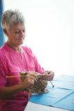 Pensionerad kvinna som gör något handarbete arkivfoton