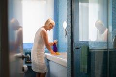 Pensionerad kvinna som gör sysslor och gör ren badrummen Royaltyfri Bild
