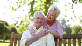 Pensionerad kvinna som omfamnar hennes make stock video