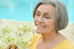 Pensionerad kvinna som poserar med blommor Royaltyfri Bild