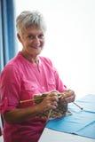 Pensionerad le kvinna som gör något handarbete arkivbilder