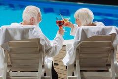 Pensionerad man och kvinna som tycker om deras liv som ligger nära pölen Fotografering för Bildbyråer