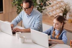 Pensionerad man och liten flicka som hemma surfar internet Fotografering för Bildbyråer