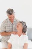 Pensionerad man som ger en massage till hans fru 库存照片