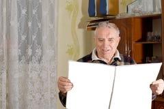 Pensionerad man som tycker om hans tidning Arkivfoto