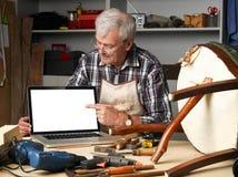 Pensionerad snickare med bärbara datorn Arkivfoton