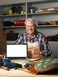 Pensionerad snickare med bärbara datorn Fotografering för Bildbyråer