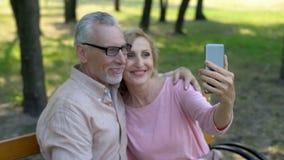 Pensionerade par som tar selfiefotoet vid smartphonen parkerar, semestrar in, minnen arkivfoto