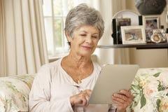 Pensionerat högt kvinnasammanträde på den Sofa At Home Using Tablet datoren Arkivbilder