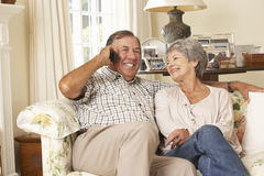 Pensionerat högt parsammanträde på det Sofa Talking On Phone At hemmet tillsammans royaltyfria foton