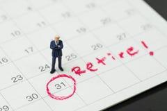 Pensioneringsdoel of het van plan zijn om met baan of financiële vrijheid, miniatuurmensenzakenman op te houden die en zich over  royalty-vrije stock fotografie