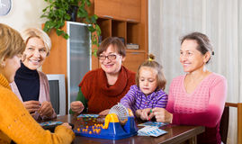 Pensioners with child playing game. Several happy female pensioners with child playing board game at home Royalty Free Stock Image