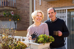 Pensioners couple outdoors. Pensioners couple on a terrace with gardening accessories and a cup of coffee stock image