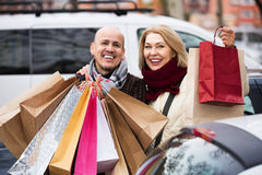 Pensioners couple with shopping bags. Positive senior couple with shopping bags near parked car Stock Photos