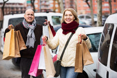Pensioners couple with shopping bags. Smiling mature couple with shopping bags near parked car Stock Image