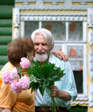 Pensioners with florets Royalty Free Stock Images