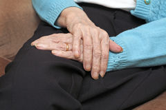 Pensioners hands. Old lady resting hands on lap wearing gold wedding ring Stock Photo