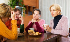 Pensioners listening to sad story Stock Photography