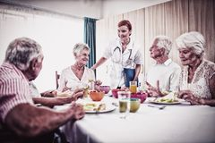 Pensioners at lunch with nurse stock photography