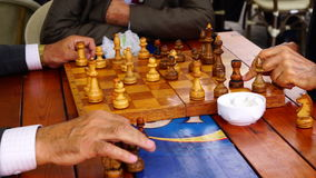 Pensioners play chess in the Park. Active retired persons, old friends and free time, two elderly men having fun and playing chess in park. Sequence of closeup stock video