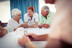 Pensioners playing cards with nurse stock images